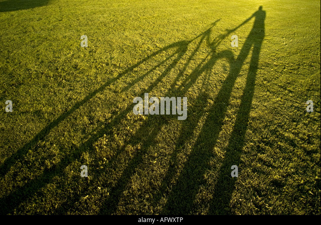 shadow of cyclist and bicycle on green grass lawn illustrating concept of green eco friendly low energy travel transport - Stock Image