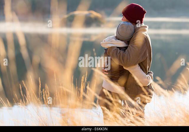 back view of lovely young couple hugging in winter - Stock Image