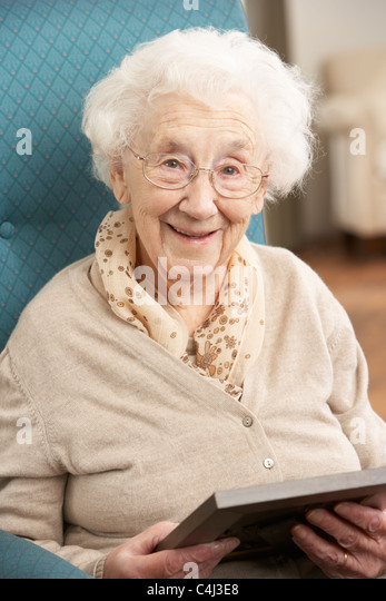 Senior Woman Looking At Photograph In Frame - Stock Image