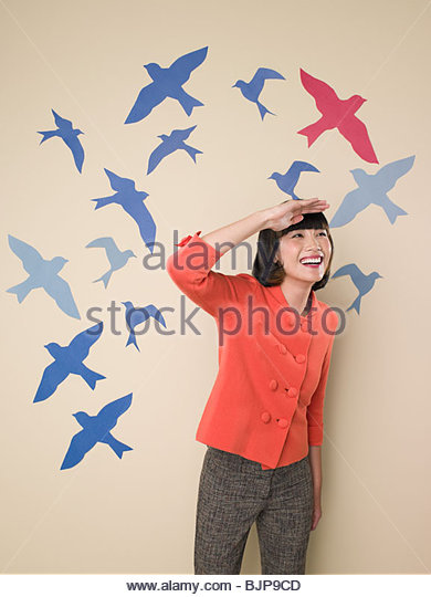 Woman with backdrop of birds - Stock Image