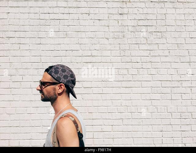 Side View Of Man Wearing Cap Standing Against Brick Wall - Stock Image