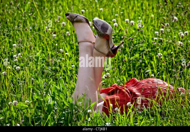 Woman in a red dress lying on a lawn and picks up the feet - Stock Image