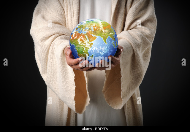 Jesus holding the world in his hands over a dark background - Stock Image