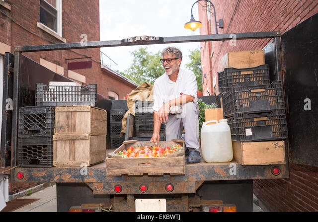 Farmer unloading crates of organic tomatoes outside grocery store - Stock Image
