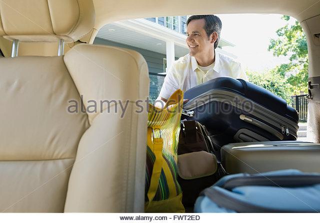 Smiling man loading luggage into back of minivan - Stock Image