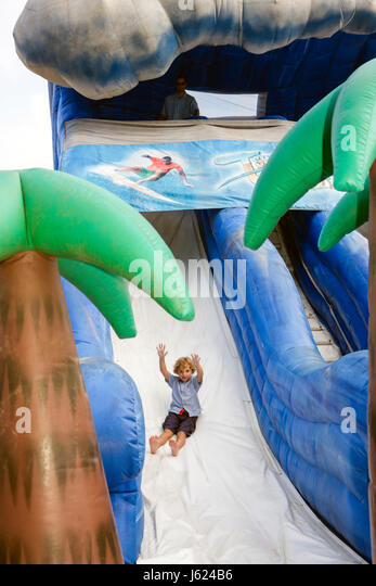 Indiana Valparaiso Zao Island Entertainment Center boy child inflatable slide fun play happy raised arms - Stock Image
