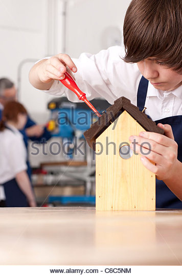Student attaching roof to birdhouse in woodworking class - Stock Image