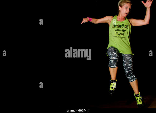Woman in Zumbathon/keep fit clothes jumps in the air - Stock Image
