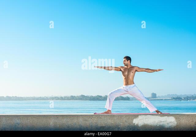 Young man practicing yoga position at Pacific beach, San Diego, California, USA - Stock-Bilder