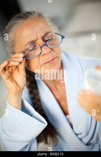 Woman wearing glasses to look at container - Stock Image