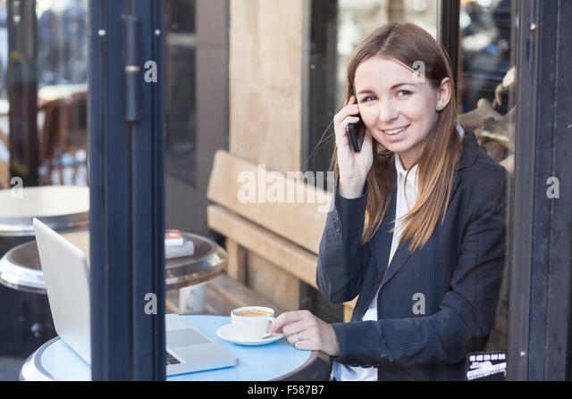 smiling business woman talking by phone in cafe - Stock-Bilder