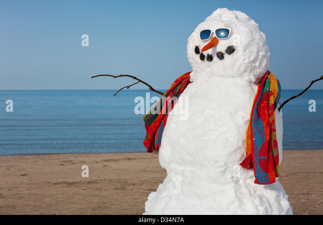 A snowman decides to go to the beach. - Stock Image