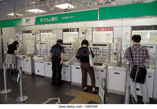 Tokyo Japan Shinjuku Post Office JP Bank kanji hiragana katakana characters symbols Japanese English customers ATM - Stock Image