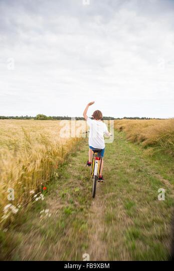 Sweden, Skane, Soderslatt, Beddinge, Boy (12-13) riding bike in wheat field - Stock Image