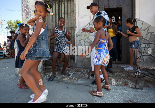 Local children dancing with their dance instructor in front of a dancing school in the street, Santiago de Cuba - Stock Image