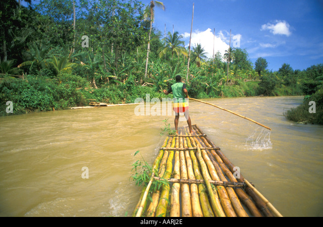 Jamaica Martha Brae River Rafting on Bamboo Raft with man poling bamboo raft on Great River near Montego Bay - Stock Image
