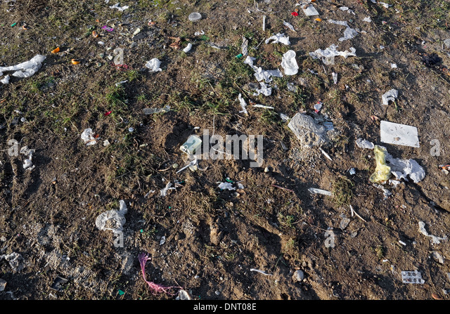 Rubbish and garbage devouring our lovely land concept background. Sunny day - Stock Image