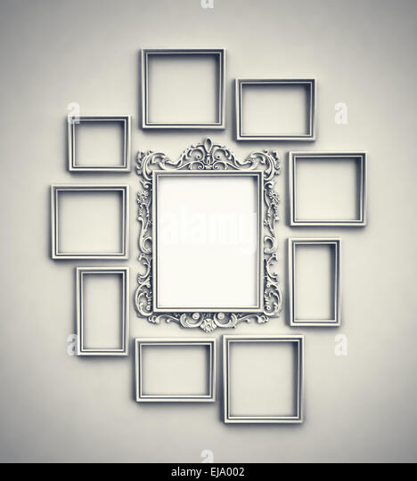 Wall with simple frames surrounding ornamented frame in the middle - Stock Image