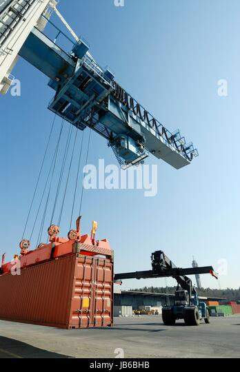 Crane lowering shipping container. - Stock-Bilder