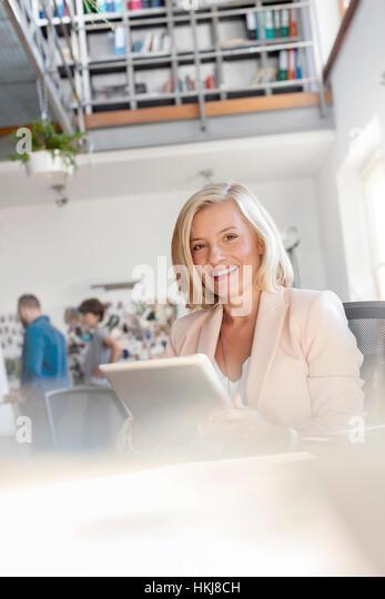 Portrait smiling female design professional using digital tablet in office - Stock-Bilder