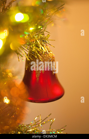 Red bell ornament hanging on illuminated Christmas tree, close up - Stock Image