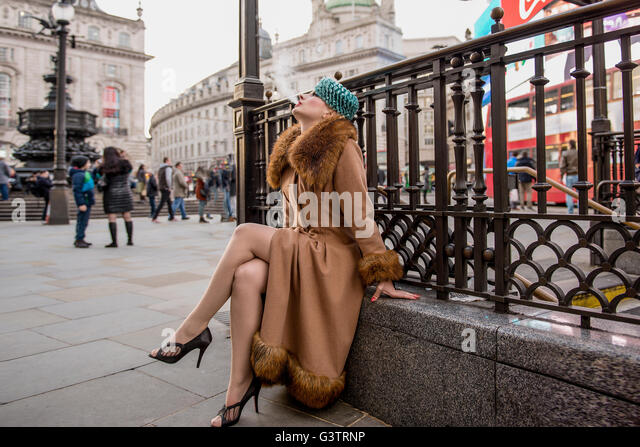 A stylish young woman dressed in 1930s style clothing sitting smoking by railings at the entrance to Piccadilly - Stock-Bilder