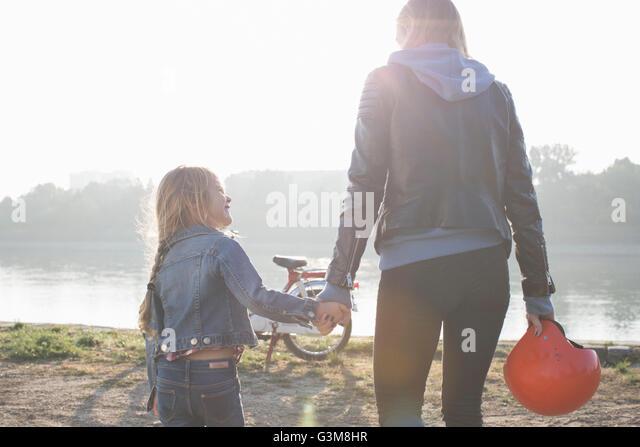 Mother and daughter, holding hands, beside lake, rear view - Stock Image