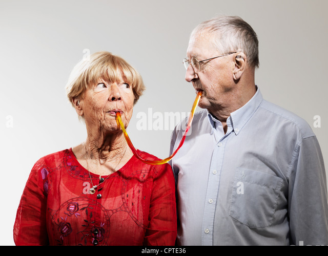 Senior couple sharing confectionery against white background - Stock Image