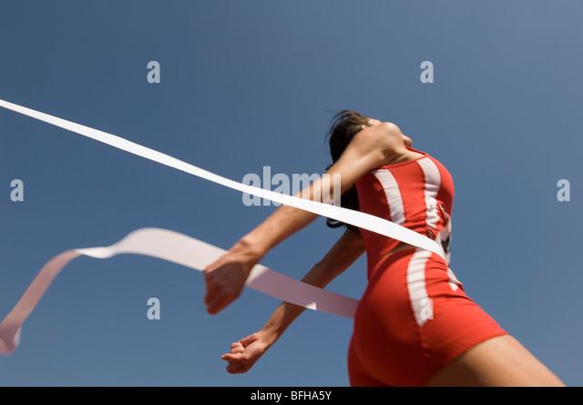 Female track athlete crossing finishing line - Stock Image