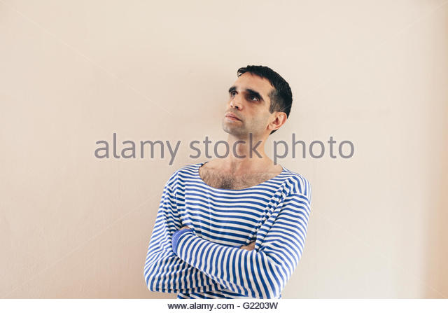 Poetic sailor dressed in blue and white striped long sleeved shirt, looking up arms crossed at his chest on a wall - Stock Image