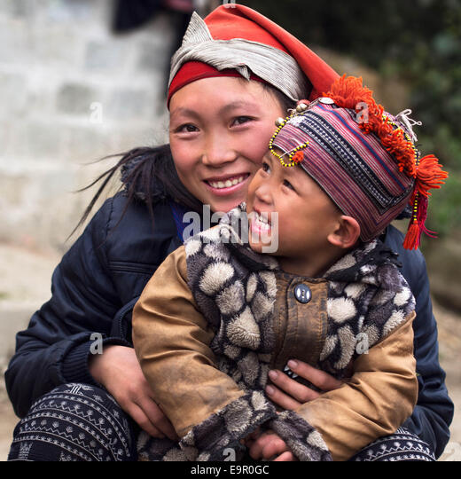 Happy Hmong woman and child smiling, sitting outside at Giang Ta Chai village near Sapa Town, Lao Cai Province, - Stock-Bilder