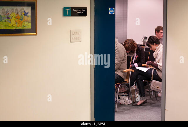 Seen through an open door young people are filling out a form - Stock Image