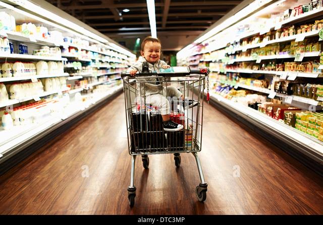 Baby boy sitting in supermarket trolley - Stock-Bilder