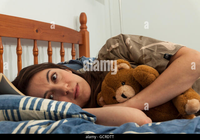 An upset young woman hugs a teddy bear in bed - Stock Image
