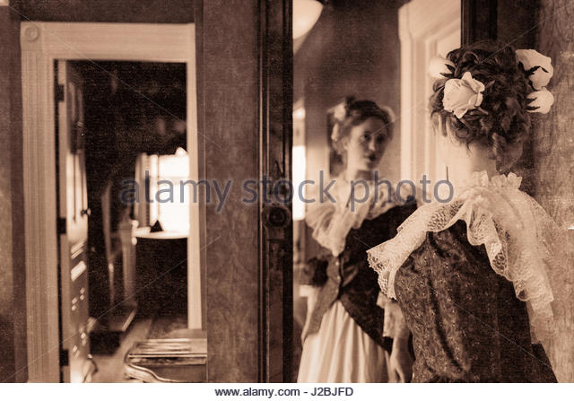 Reflection of a Victorian woman looking into a mirror - Stock Image