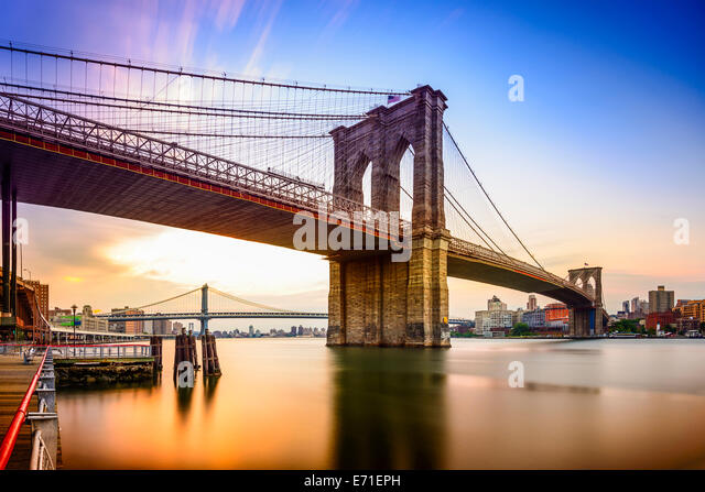 New York City, USA at the Brooklyn Bridge and East River at dawn. - Stock-Bilder