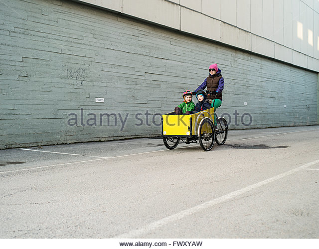 Finland, Uusimaa, Helsinki, Mother pushing two sons (2-3, 4-5) in cart - Stock Image