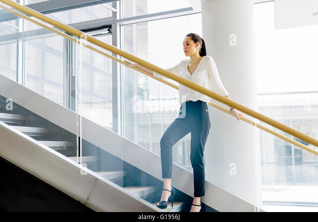Businesswoman on stairs in a modern office - Stock Image