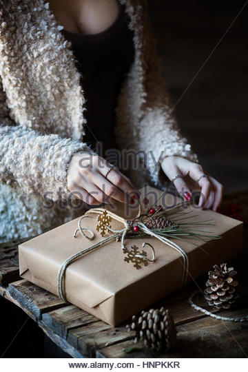 Woman wrapping a Christmas present - Stock Image
