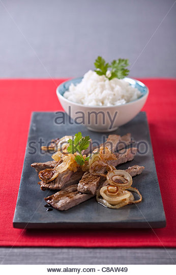 Beef fried with soya sauce and a bowl of white rice - Stock Image
