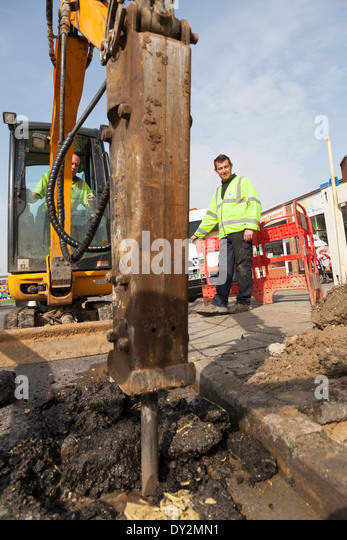 Water company workmen digging up road in town centre. - Stock Image
