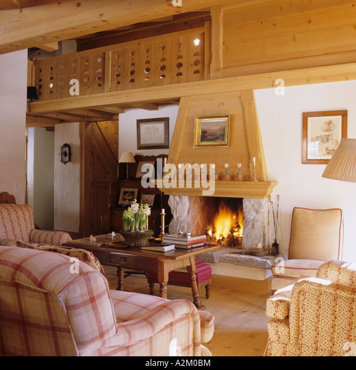 Open fireplace in sitting room of a traditional chalet in Switzerland - Stock Image