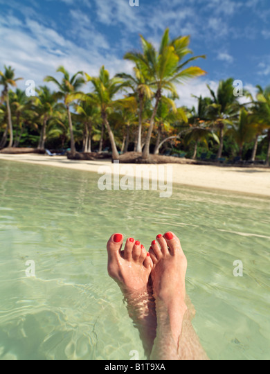 Dominican Republic Punta Cana Bavaro Beach woman s feet floating in water against a palm fringed beach - Stock Image