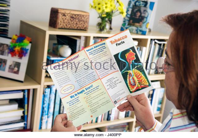Miami Beach Florida Hispanic woman reading brochure tobacco facts information anti-smoking health wellness lungs - Stock Image