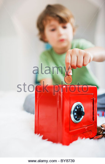 Boy putting coin into safe piggy bank - Stock Image