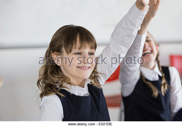 Smiling school girl with hand raised in classroom - Stock Image