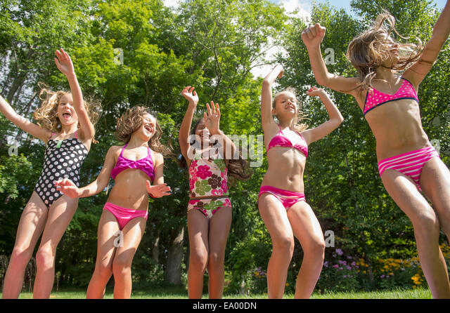Girls in swimming costume jumping in garden - Stock Image