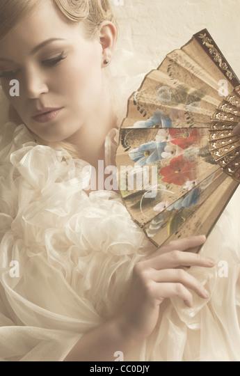 Beautiful woman holding a fan - Stock Image