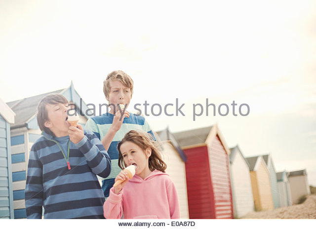Three children next to beach huts eating ice cream cones, Southwold, Sussex, UK - Stock-Bilder
