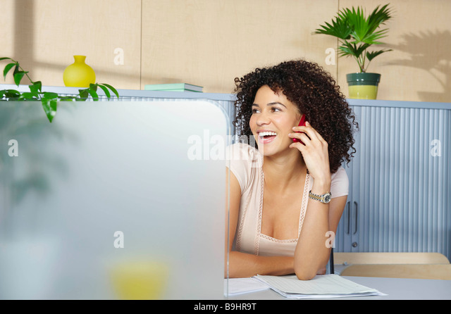 Young woman on phone at desk in office - Stock-Bilder